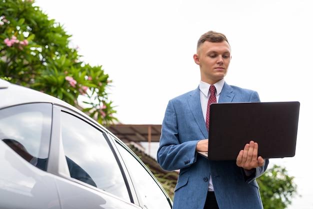 Jonge zakenman met laptop in de straten buiten