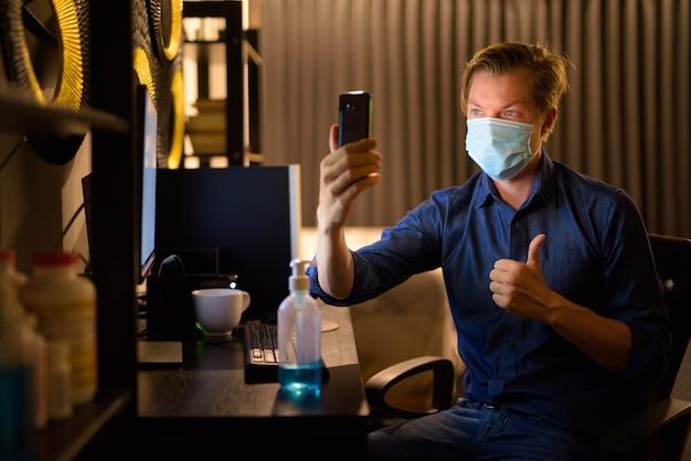 Jonge zakenman met masker duimen opgevend en videobellen tijdens het werken vanuit huis 's avonds laat