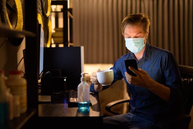 Jonge zakenman met masker koffie houden en telefoon thuis gebruiken tijdens het werken 's avonds laat