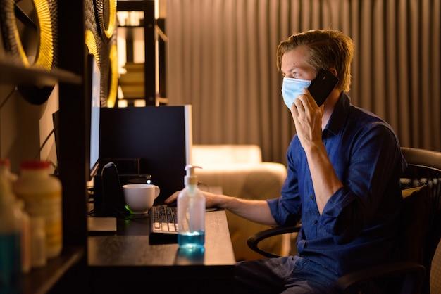 Jonge zakenman met masker praten aan de telefoon tijdens het werken vanuit huis 's nachts