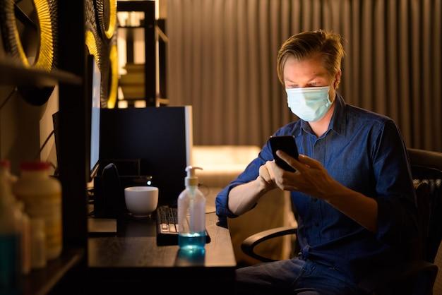 Jonge zakenman met masker thuis met behulp van telefoon tijdens het werken 's nachts