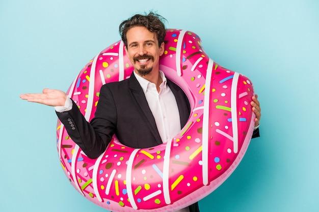 Jonge zakenman met opblaasbare donut geïsoleerd op blauwe achtergrond met een kopie ruimte op een palm en met een andere hand op de taille.