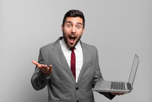 Jonge zakenman met open mond en verbaasd, geschokt en verbaasd met een ongelooflijke verrassing en met een laptop vast