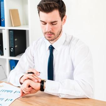 Jonge zakenman met pen in de hand kijken naar de tijd op polshorloge