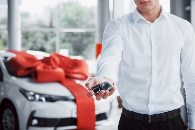 Jonge zakenman met sleutels in zijn handen, koopt een auto in de cabine.