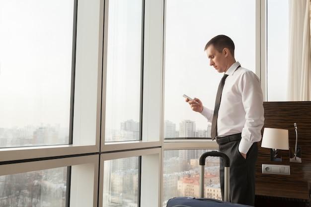 Jonge zakenman met smartphone in hotelkamer