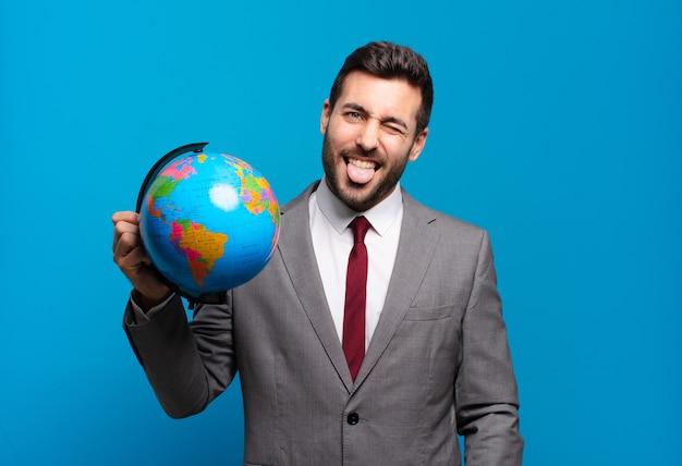 Jonge zakenman met vrolijke, zorgeloze, rebelse houding, grappen maken en tong uitsteken, plezier hebben met een wereldbolkaart