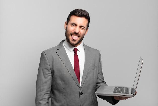 Jonge zakenman met vrolijke, zorgeloze, rebelse houding, grappen maken en tong uitsteken, plezier maken en een laptop vasthouden