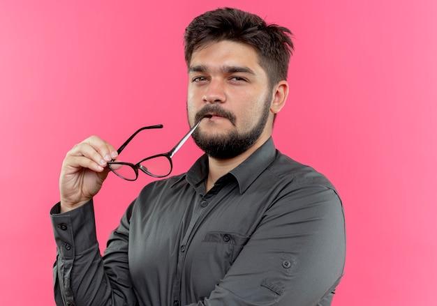 Jonge zakenman mond met een bril aan te raken die op roze muur wordt geïsoleerd