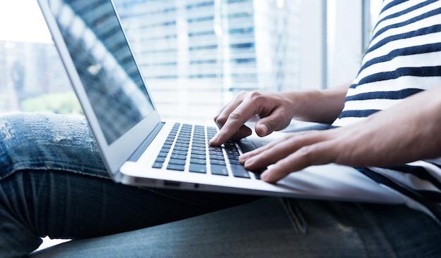 Jonge zakenman multitasking met behulp van laptop