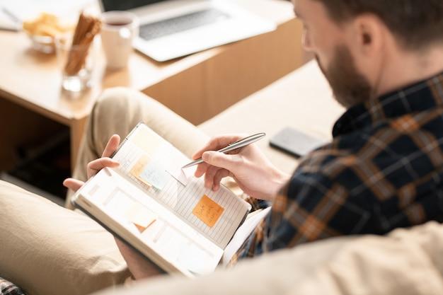 Jonge zakenman notities maken op stickie in notitieblok tijdens het organiseren van werk of het plannen van nieuwe afspraken