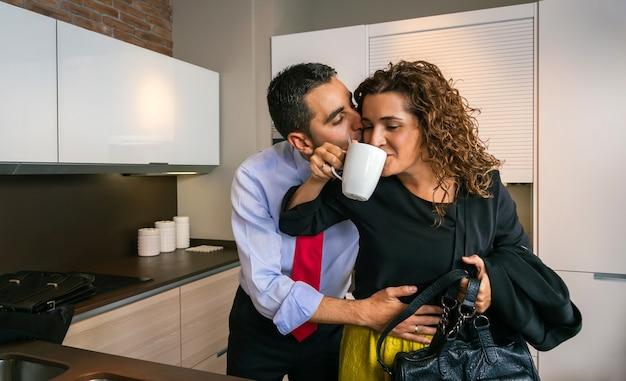 Jonge zakenman omhelst en kust een gelukkige gekrulde vrouw terwijl hij een snelle kop koffie drinkt voordat hij naar zijn werk gaat