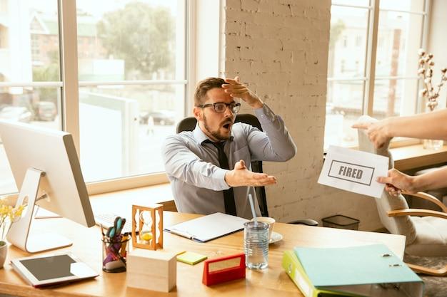 Jonge zakenman ontslagen, kijkt boos. moet zijn kantoorspullen inpakken en de werkplek verlaten voor een nieuwe werknemer. problemen in beroep, stress, werkloosheid, nieuwe manier van leven of einde loopbaan.
