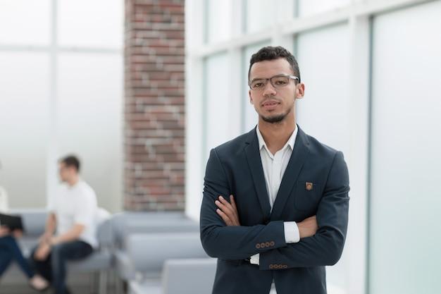 Jonge zakenman op de achtergrond van een modern kantoor. foto met kopieerruimte