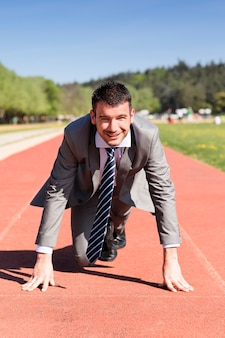 Jonge zakenman op een atletiekbaan in de zomer