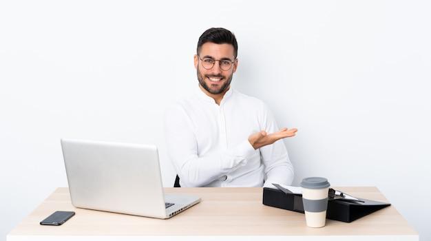 Jonge zakenman op een werkplek die een idee presenteert terwijl het glimlachen naar