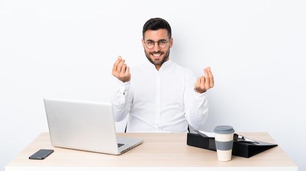 Jonge zakenman op een werkplek die geldgebaar maakt