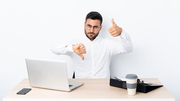 Jonge zakenman op een werkplek die goed-slecht teken maakt. onbeslist tussen ja of niet