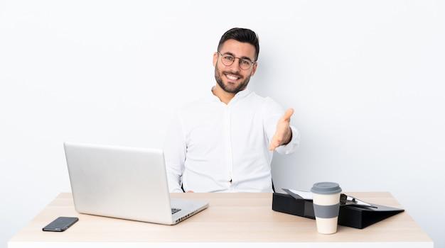 Jonge zakenman op een werkplek handen schudden voor het sluiten van een goede deal
