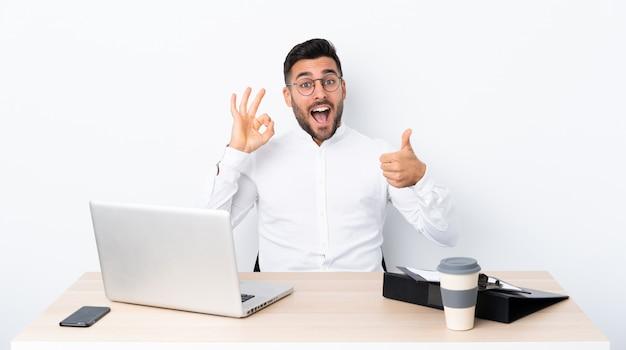 Jonge zakenman op een werkplek met ok teken en duim omhoog gebaar