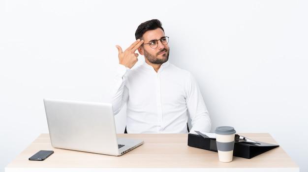 Jonge zakenman op een werkplek met problemen die zelfmoordgebaar maken