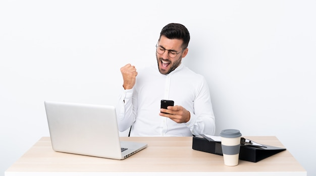 Jonge zakenman op een werkplek met telefoon in overwinning positie