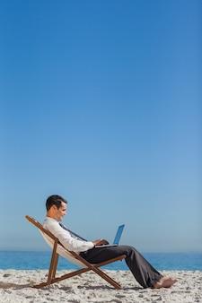 Jonge zakenman op zijn ligstoel die zijn laptop met behulp van
