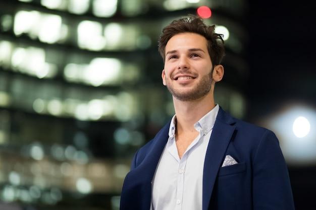 Jonge zakenman openlucht in een moderne stad die bij nacht plaatst