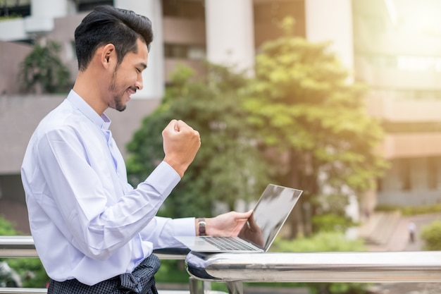 Jonge zakenman opgewonden steekt hand op, wees blij en lacht met laptop naar urban
