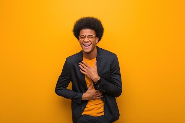 Jonge zakenman over een oranje muur die en pret lacht heeft