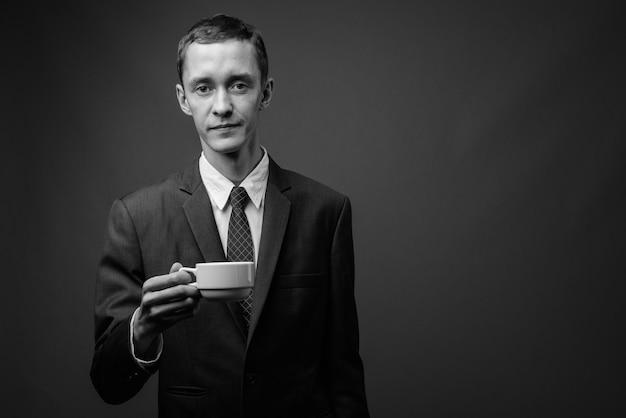 Jonge zakenman pak dragen tegen grijze muur in zwart en wit