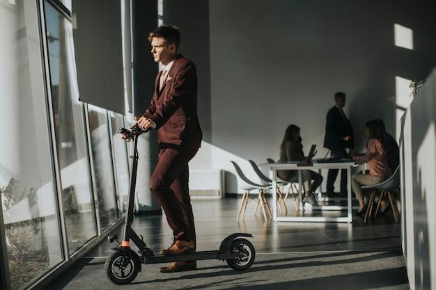 Jonge zakenman permanent door het loket met elektrische scooter