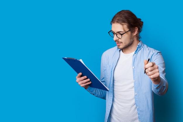 Jonge zakenman poseert op een blauwe muur met vrije ruimte, kijkt in een map en houdt een pen vast