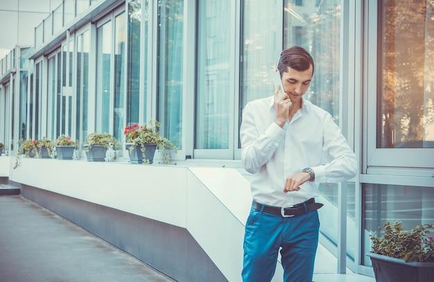 Jonge zakenman praten aan de telefoon door business center