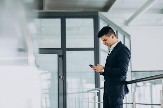 Jonge zakenman praten over de telefoon in het kantoor