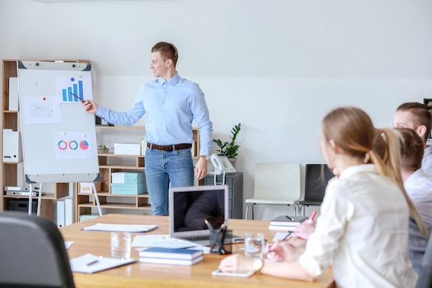 Jonge zakenman presentatie geeft tijdens bijeenkomst in kantoor