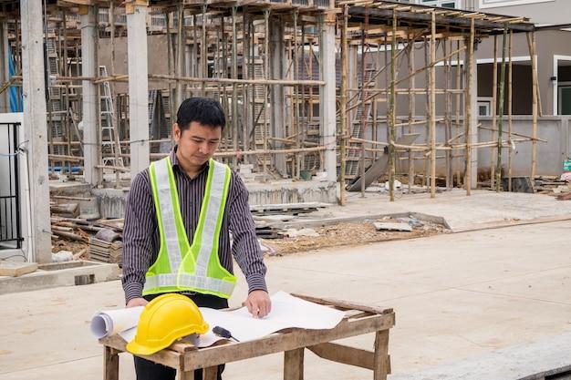 Jonge zakenman professionele ingenieur werknemer op de bouwplaats huis bouwen met blauwdruk
