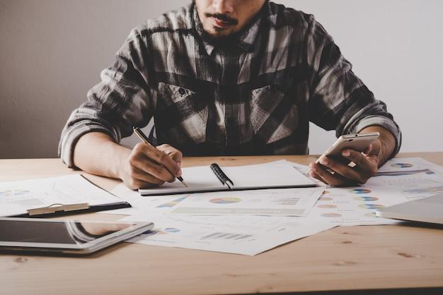 Jonge zakenman schrijft in een notitieboekje terwijl werkanalyse bedrijfsgegevens in kantoor.