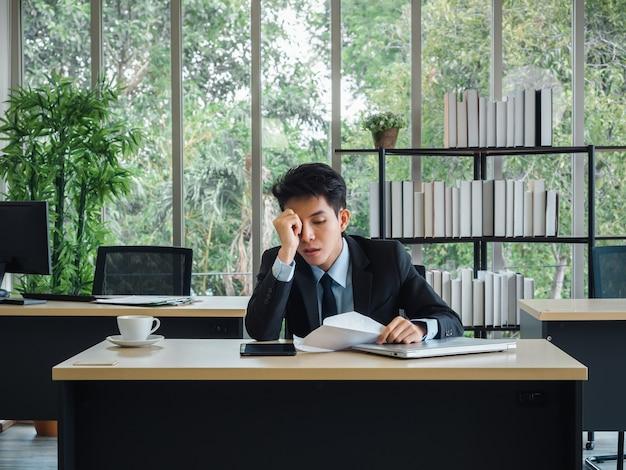 Jonge zakenman slecht nieuws ontvangen met ontslagbrief, moe, gestrest en verdrietig zitten met verstrooid op zijn bureau in kantoor.