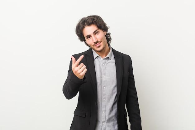 Jonge zakenman tegen een wit wijzend met vinger naar je alsof uitnodigend naderbij komen.