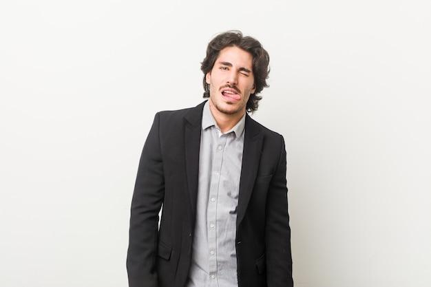 Jonge zakenman tegen een witte achtergrond grappige en vriendelijke tong uitsteekt.