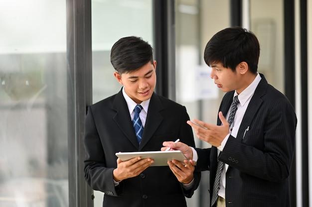 Jonge zakenman twee raadpleegt en ontmoet bedrijfsbespreking.