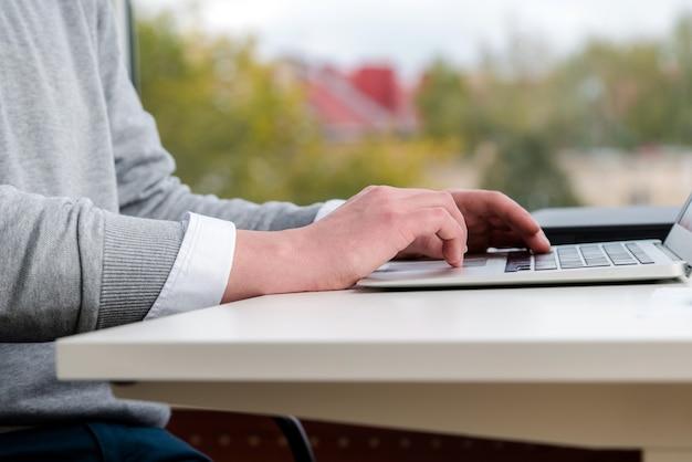 Jonge zakenman typen op laptop toetsenbord op kantoor.