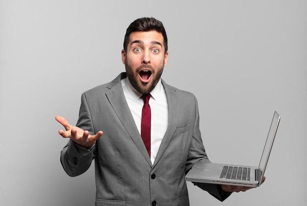 Jonge zakenman voelt zich extreem geschokt en verrast, angstig en in paniek, met een gestrest en geschokte blik en houdt een laptop vast