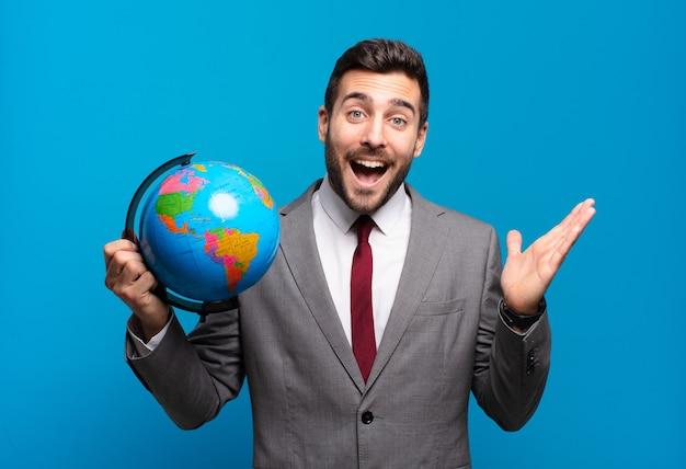 Jonge zakenman voelt zich gelukkig, verrast en opgewekt, glimlacht met een positieve houding, realiseert een oplossing of idee met een wereldbolkaart