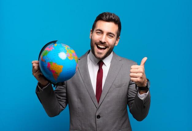 Jonge zakenman voelt zich trots, zorgeloos, zelfverzekerd en gelukkig, positief glimlachend met duimen omhoog met een wereldbolkaart