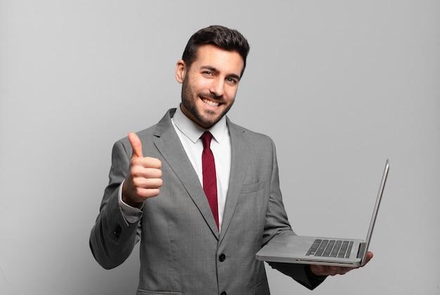 Jonge zakenman voelt zich trots, zorgeloos, zelfverzekerd en gelukkig, positief glimlachend met duimen omhoog