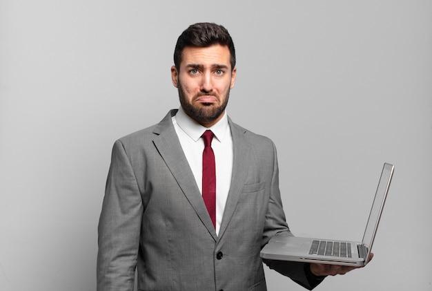 Jonge zakenman voelt zich verdrietig en zeurt met een ongelukkige blik, huilt met een negatieve en gefrustreerde houding en houdt een laptop vast