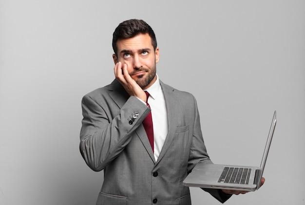 Jonge zakenman voelt zich verveeld, gefrustreerd en slaperig na een vermoeiende, saaie en vervelende taak, gezicht met de hand vasthoudend en een laptop vasthoudend