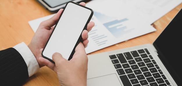 Jonge zakenman werkt aan zijn project tijdens het gebruik van smartphone met leeg scherm